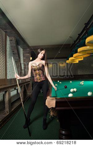 sexy girl in corset plays billiards.
