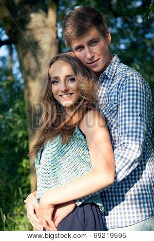 Young Couple In Nature On Summer, Looking Into The Camera