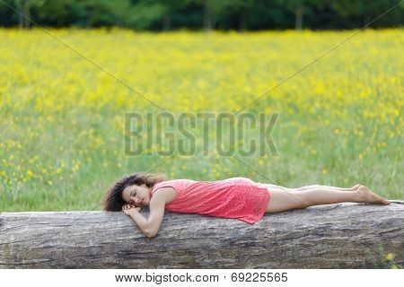 Beautiful young woman sleeping on a log or tree trunk in a rural field full of colorful yellow summer flowers as she relaxes and unwinds after an exhausting day in the peace of the countryside