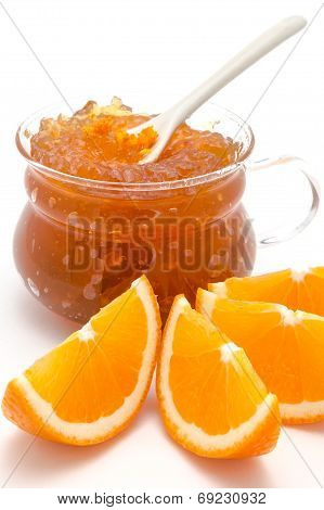 Sliced oranges and orange jam in glass recipient, isolated on a white background