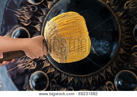 Hand hit big gong in temple