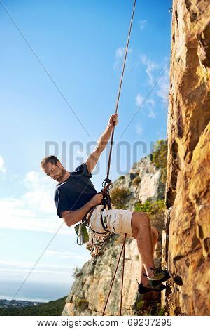 A rock climber going down a steep mountain with a rope against a blue sky