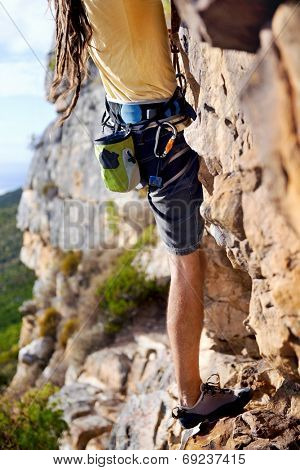Cropped image of a man with dreadlocks finding a foothold on a steep mountain