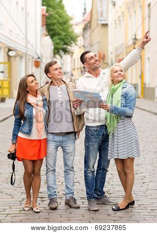travel, vacation, technology and friendship concept - group of smiling friends with map and photocamera exploring city