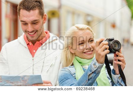 travel, vacation, technology and friendship concept - smiling couple with map and photocamera exploring city