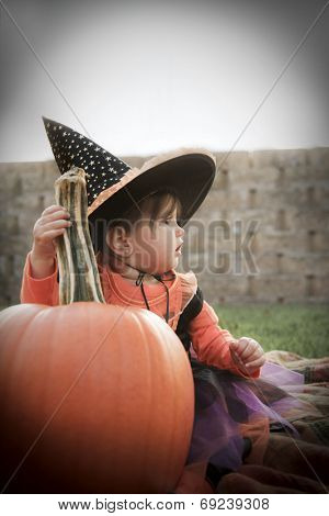 Halloween Greeting with a baby witch holding a pumpkin