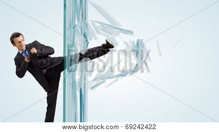 Young determined businessman breaking glass with karate kick
