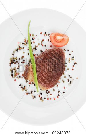 meat savory : grilled beefsteak served with red tomato allspice pepper green chives on plate isolated over white background