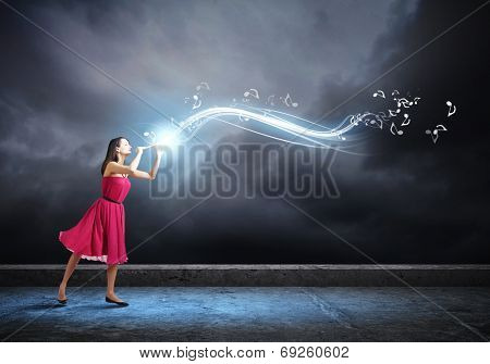 Young woman in red dress in darkness playing fife