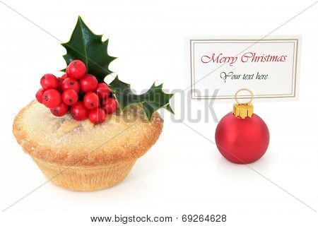 Christmas mince pie cake with holly and red bauble with name place setting tag over white background.