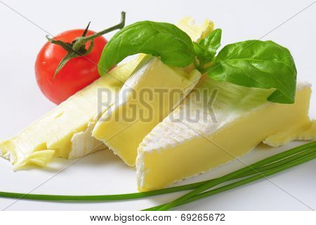 pieces of cow's milk cheese with herbs and tomatoes