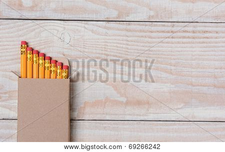 High angle shot of a cardboard box of new pencils on a whitewashed wood desk. The box is set ot the right leaving lots of copy space. Ideal for Back to School projects.