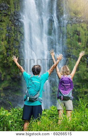 Couple having fun together outdoors on hike. Looking up at incredible waterfall in Hawaii.