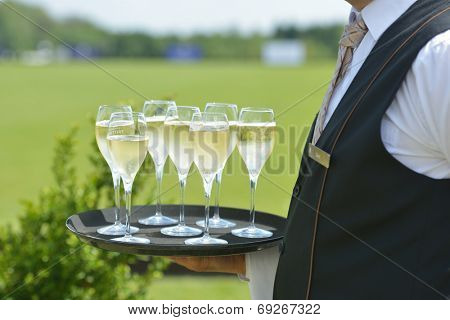 TSELEEVO, MOSCOW REGION, RUSSIA - JULY 26, 2014: Waiter holds the tray with champagne for the guests of the British Polo Day. It was the second British Polo Day in Russia