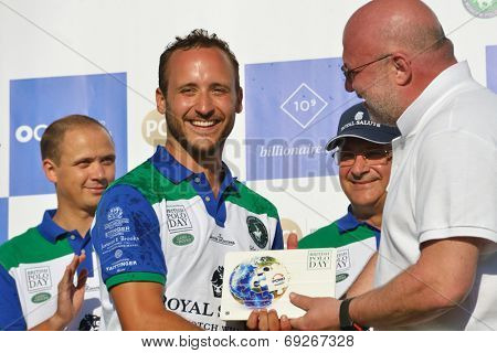 TSELEEVO, MOSCOW REGION, RUSSIA - JULY 26, 2014: Misha Rodzianko receives the winner's prise during the British Polo Day. Tseleevo Golf & Polo Club hosts the event for the second time