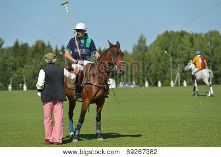 TSELEEVO, MOSCOW REGION, RUSSIA - JULY 26, 2014: Voice of British Polo Day Simon Ledger talks with Jamie Hepburn of Oxbridge polo team. It was the second British Polo Day in Russia
