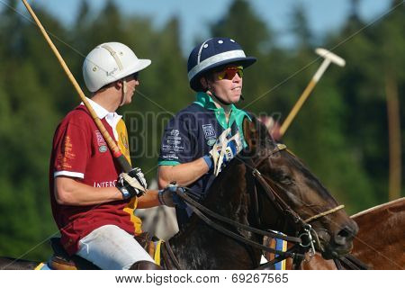 TSELEEVO, MOSCOW REGION, RUSSIA - JULY 26, 2014: Sam Browne of Oxbridge Polo Team (right) and Pavel Isayev of Tseleevo Polo Club talking between chukkers during the British Polo Day. Oxbridge won 5-4