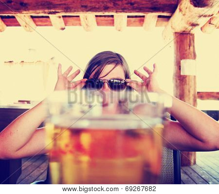 woman peeking over a fresh draft beer toned with a vintage retro style instagram filter