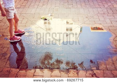 a city building reflected in the puddle with a young girl splashing in the water toned with a vintage instagram filter
