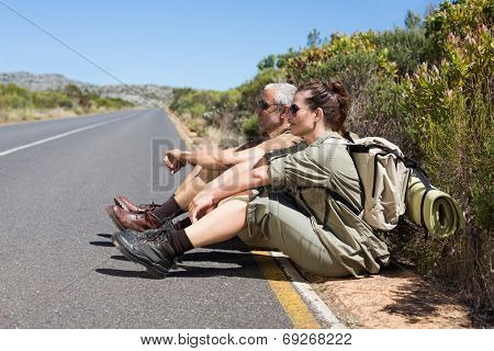Hiking couple sitting on the side of the road on a sunny day