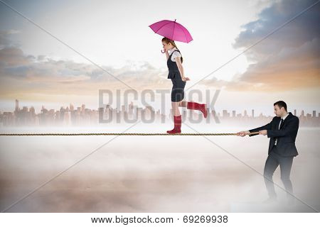 Young businessman pulling a tightrope for businesswoman against cityscape on the horizon