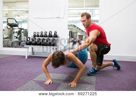 Personal trainer with client doing push up on exercise ball at the gym