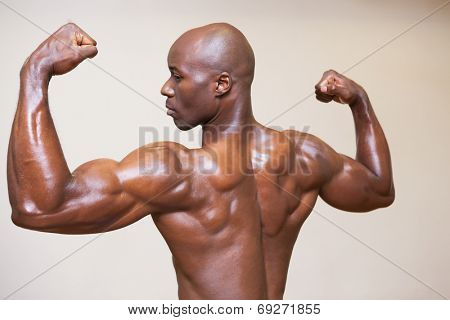 Shirtless young muscular man flexing muscles over white background