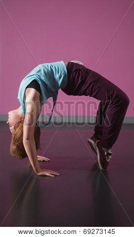 Pretty break dancer doing a back bend in the dance studio