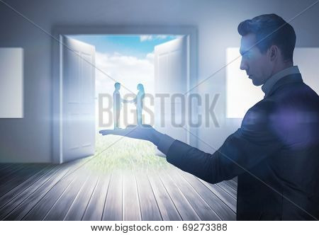 Composite image of businessman holding business partners against open doors leading to sunny landscape