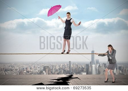 Young business woman pulling a tightrope for businesswoman against cracked balcony overlooking city
