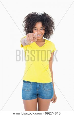 Pretty girl in yellow tshirt and denim hot pants pointing at camera on white background