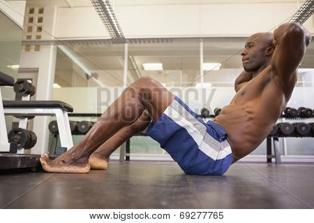 Full length side view of muscular man doing abdominal crunches in gym
