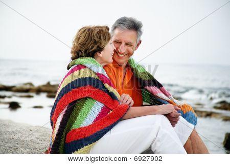 Mature couple sitting on the beach.