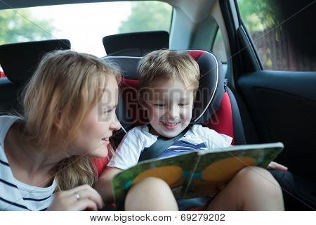 Boy holding book sitting in a car with mother