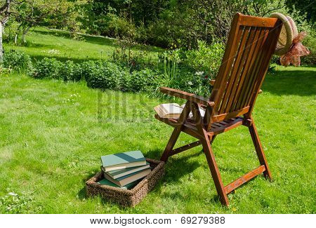 Wooden Chair Books And Hat In Garden