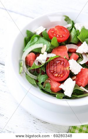 Salad with watermelon, onion, arugula and spinach leaves on plate, on wooden background
