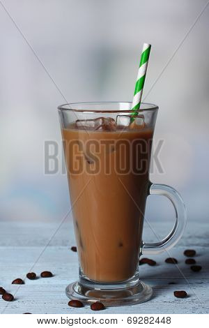 Glass of iced milk coffee on light background