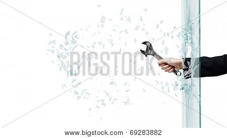 Close up of male hand breaking glass with wrench