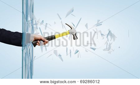 Close up of male hand breaking glass with hammer
