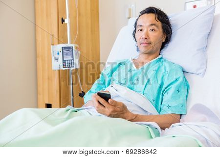 Portrait of mature male patient holding mobile phone while resting on bed in hospital