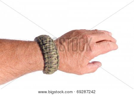 Mans arm with a double cobra weave survival bracelet in camouflage paracord, isolated over white