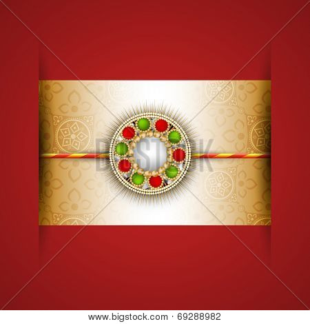 Beautiful red and green pearl decorated rakhi on beige and red background for celebrations of Raksha Bandhan festival.