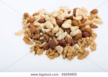 mixed nuts - hazelnuts walnuts cashews pine nuts isolated on white background