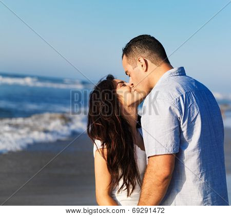 romantic couple kissing each other on the beach.