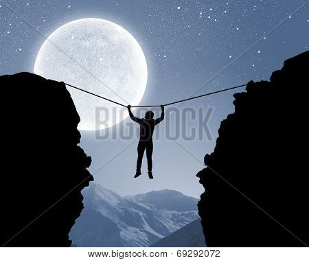 Silhouette of man hanging on rope above mountain gap