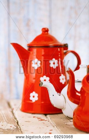 vintage Red and white Enamel Tea Coffee Pots on old wooden table
