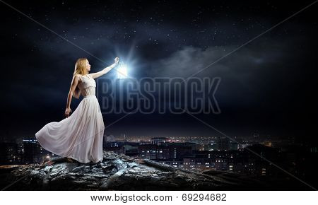 Young woman in white long dress with lantern