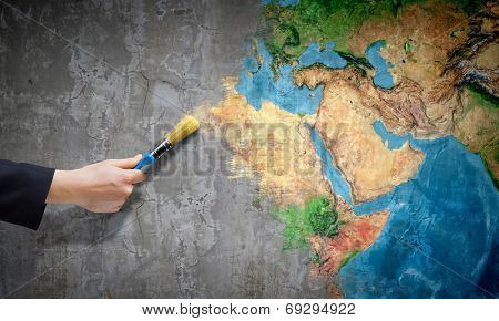 Close up of hand painting Earth planet with brush. Elements of this image are furnished by NASA