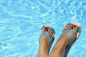 stock photo of wet feet  - Female wet feet with flip flops by the pool - JPG