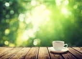 stock photo of wood  - cup coffee and sunny trees background - JPG